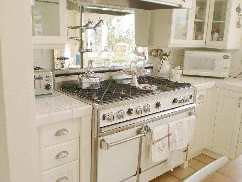 Fehér vintage konyha csodálatos tűzhellyel és elegáns konyhai kiegészítőkkel
